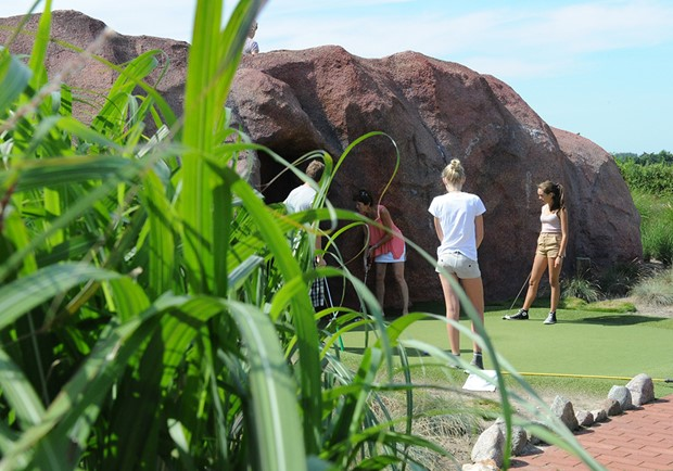Visitors playing Adventure Golf into a cave